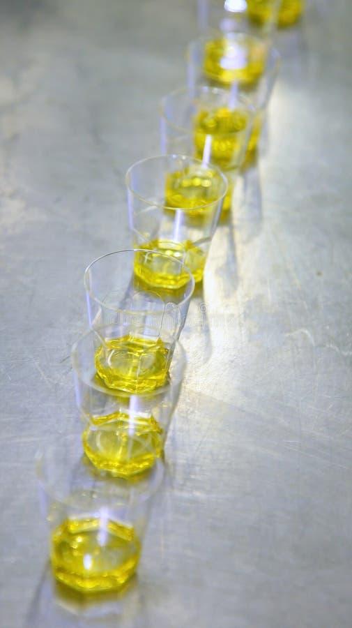 在玻璃杯子的橄榄油品尝的 钢桌在意大利餐馆的厨房里 库存图片