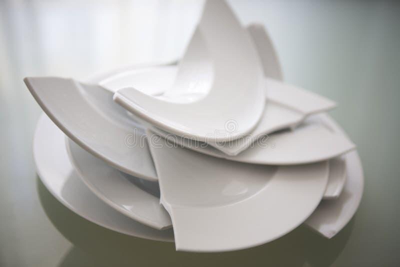 在玻璃桌上的残破的白色板材 免版税库存照片