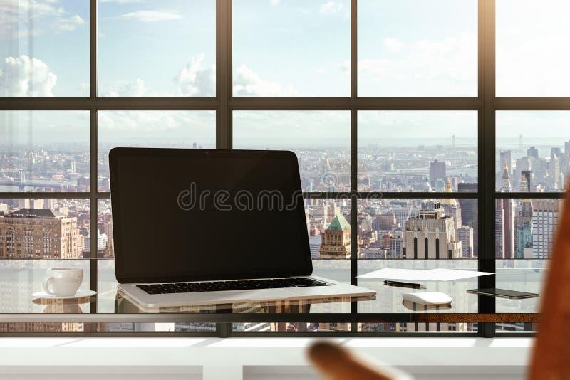 在玻璃桌上的空白的膝上型计算机在一个现代办公室和城市视图 库存照片