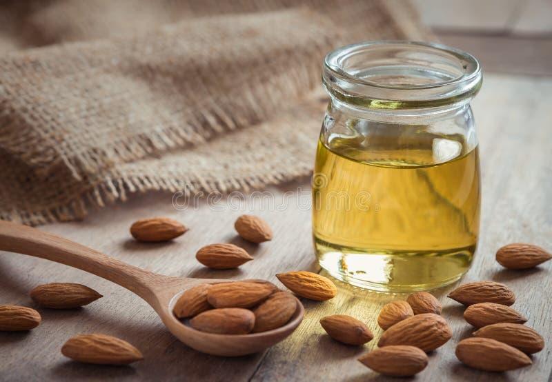 在玻璃瓶和杏仁的扁桃仁油在木桌上 免版税库存图片