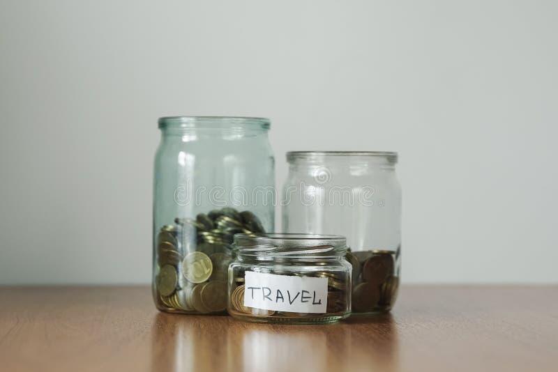在玻璃瓶子不同的需要的,钱箱的硬币 现金储款概念的发行 旅行贴纸 库存照片
