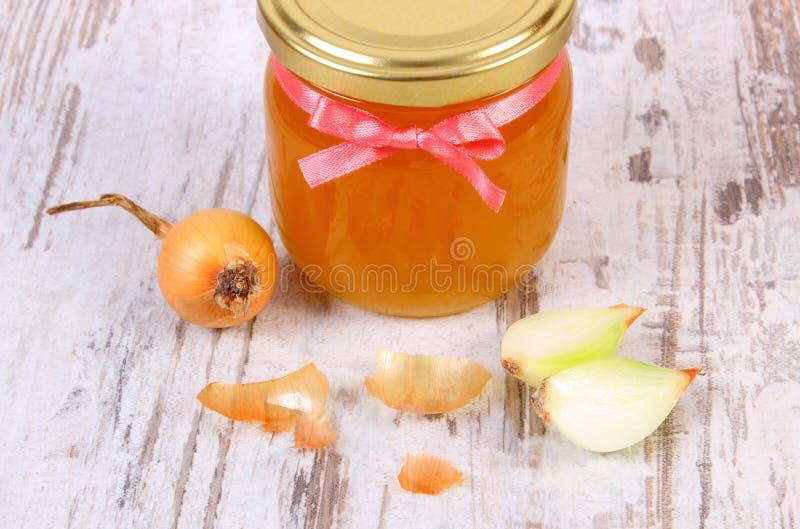 在玻璃瓶子和葱的新鲜的有机蜂蜜在木背景,健康营养和加强免疫 免版税图库摄影