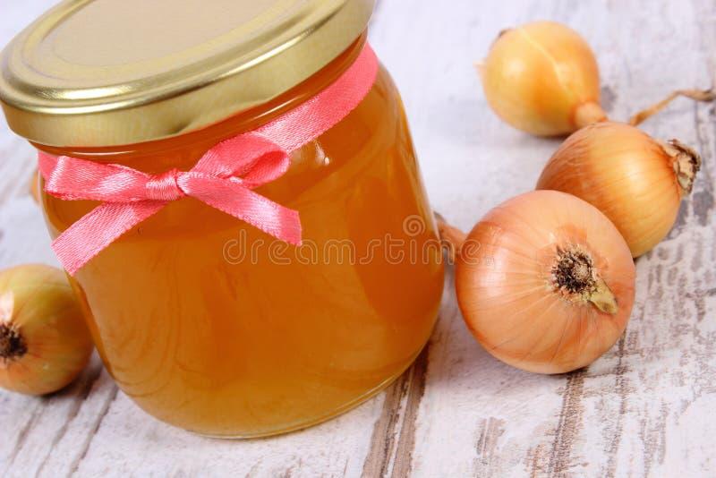 在玻璃瓶子和葱的新鲜的有机蜂蜜在木背景,健康营养和加强免疫 库存照片