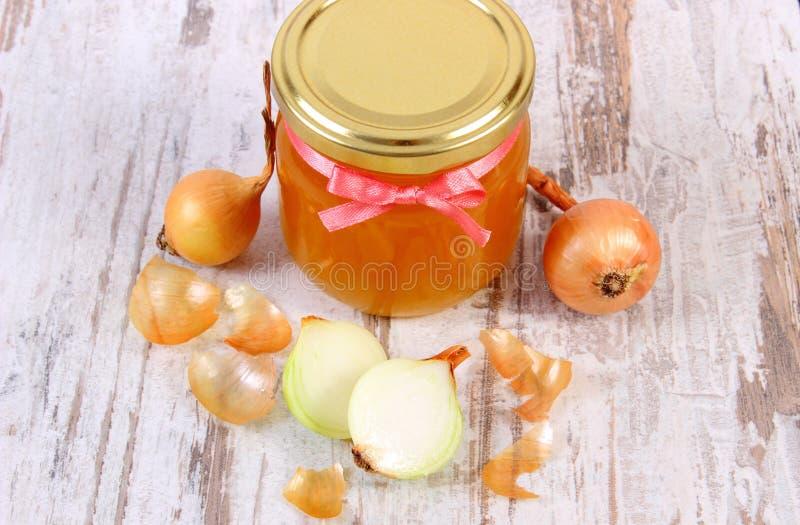 在玻璃瓶子和葱的新鲜的有机蜂蜜在木背景,健康营养和加强免疫 免版税库存图片