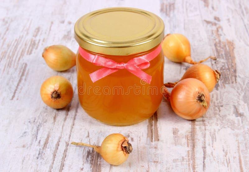 在玻璃瓶子和葱的新鲜的有机蜂蜜在木背景,健康营养和加强免疫 库存图片