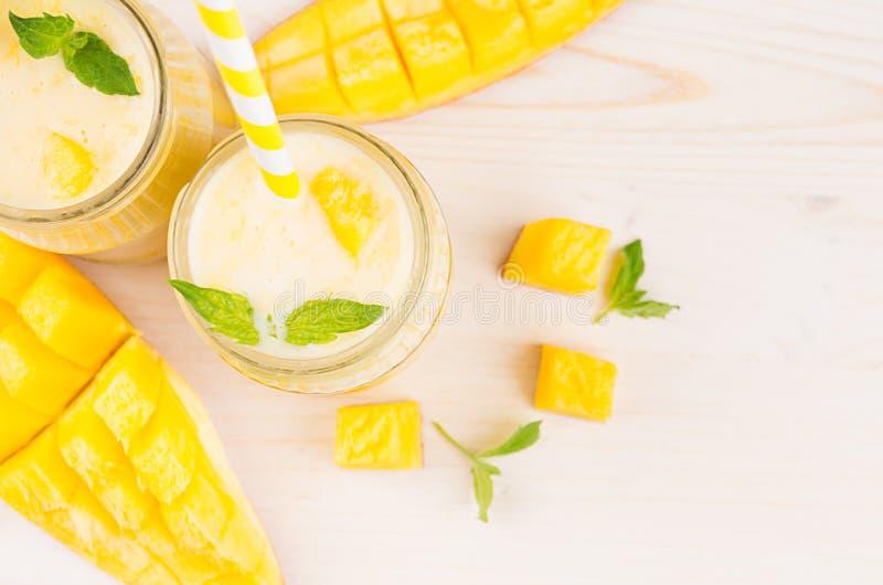 在玻璃瓶子有秸杆的,薄荷叶,芒果切片,关闭的新近地被混和的黄色芒果果子圆滑的人,顶视图 免版税库存图片