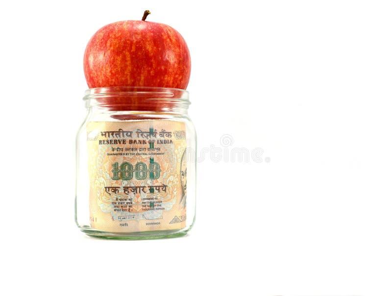 在玻璃瓶子的印地安金钱用在瓶子,得到股息或回归的概念顶部的红色水多的苹果从您的金钱 免版税库存照片