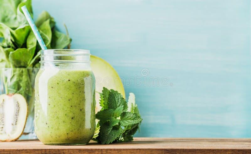 在玻璃瓶子的新近地被混和的绿色果子圆滑的人有秸杆的 库存图片