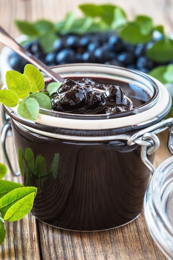在玻璃瓶子的蓝莓果酱在木桌上 免版税库存图片