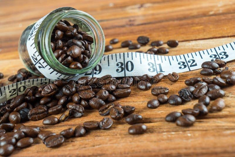 在玻璃瓶的咖啡豆有在木backgrou的卷尺的 免版税库存照片