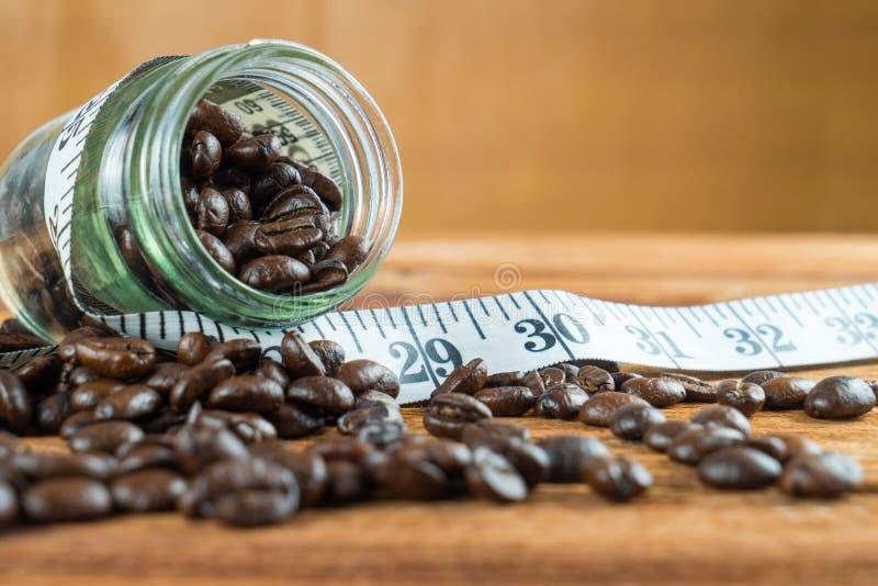 在玻璃瓶的咖啡豆有在木backgrou的卷尺的 库存图片