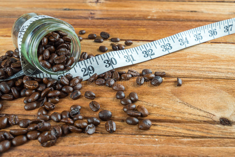在玻璃瓶的咖啡豆有在木backgrou的卷尺的 免版税库存图片