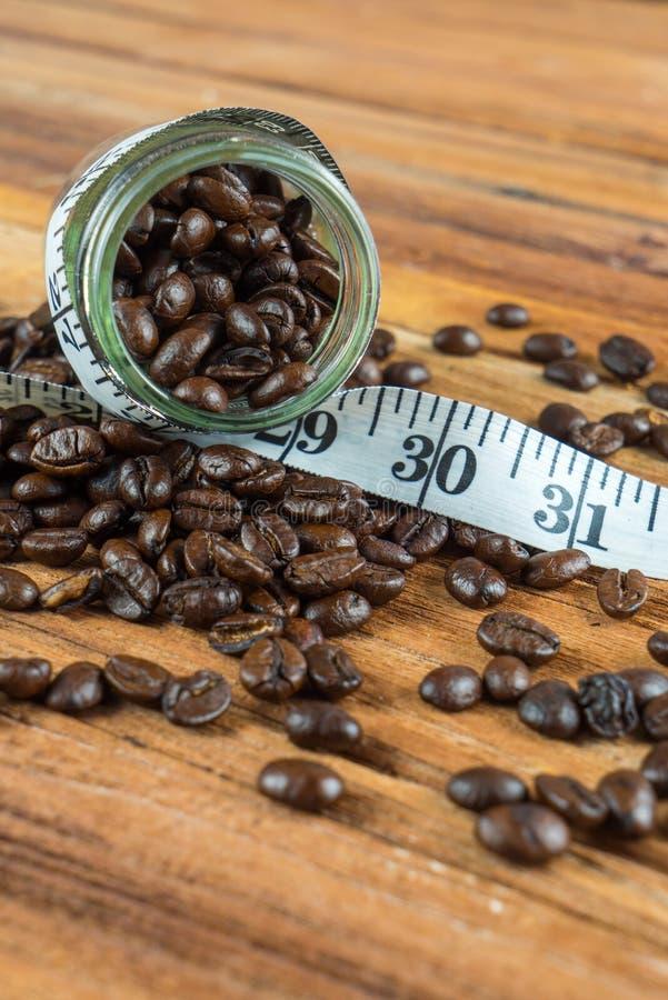 在玻璃瓶的咖啡豆有在木backgrou的卷尺的 免版税图库摄影