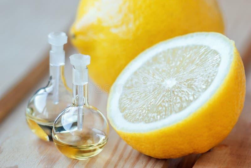 在玻璃瓶的根本芳香油用在木背景的新鲜,水多的柠檬果子 浴秀丽构成油用肥皂擦洗处理 温泉概念 有选择性的f 免版税图库摄影