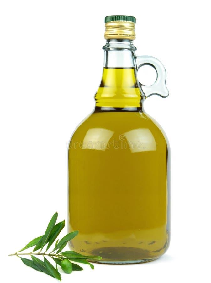 在玻璃瓶的额外处女橄榄油有在白色背景隔绝的绿橄榄分支的 库存图片