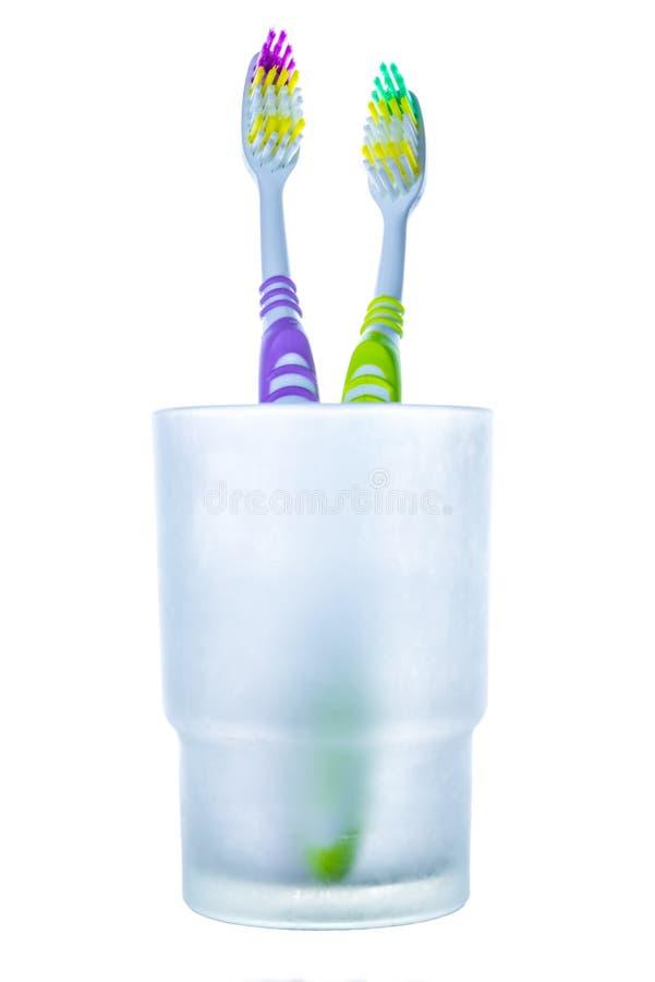 在玻璃的两把五颜六色的牙刷 免版税库存图片