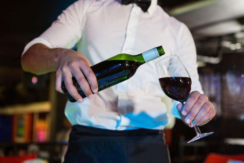 在玻璃的侍者倾吐的酒 免版税库存图片