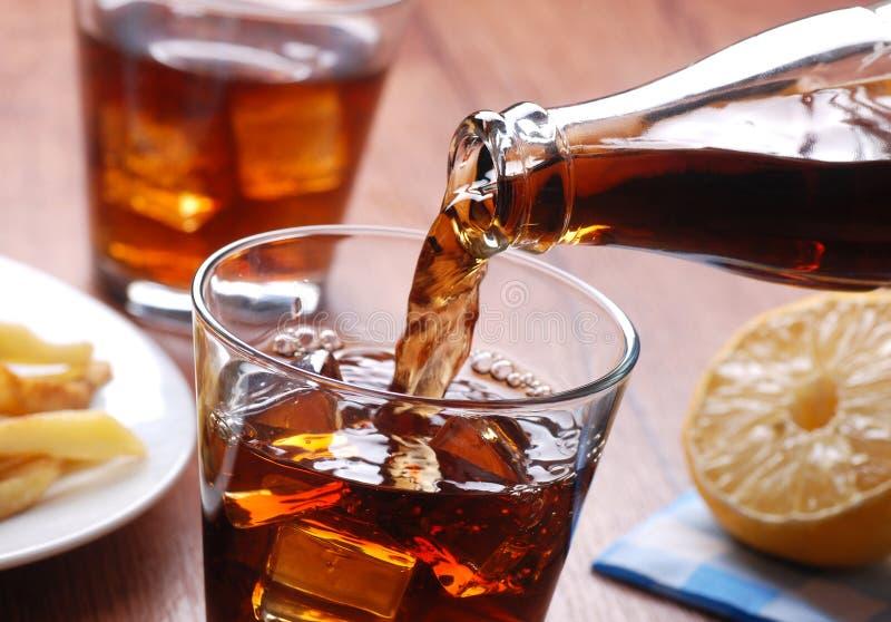 在玻璃的倾吐的可乐 库存图片