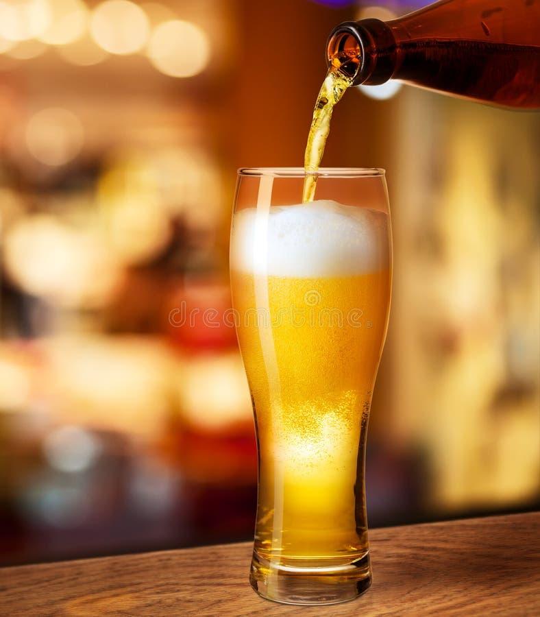 在玻璃的倾吐的啤酒在酒吧书桌上 免版税库存图片