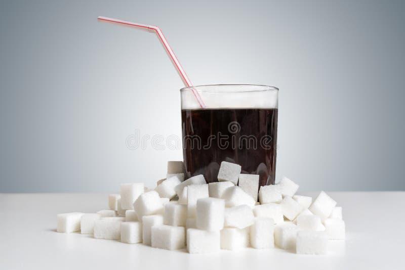 在玻璃的可乐饮料和许多加糖立方体  概念吃不健康 免版税库存照片