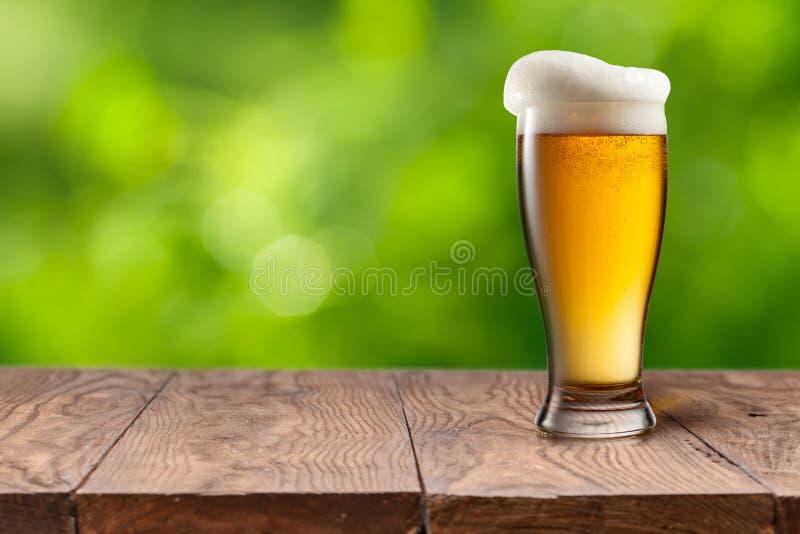 在玻璃的啤酒在反对绿色的木桌上 免版税库存图片