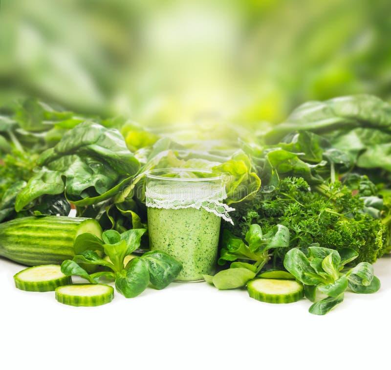 在玻璃的圆滑的人在白色桌上的绿色菜背景 库存照片