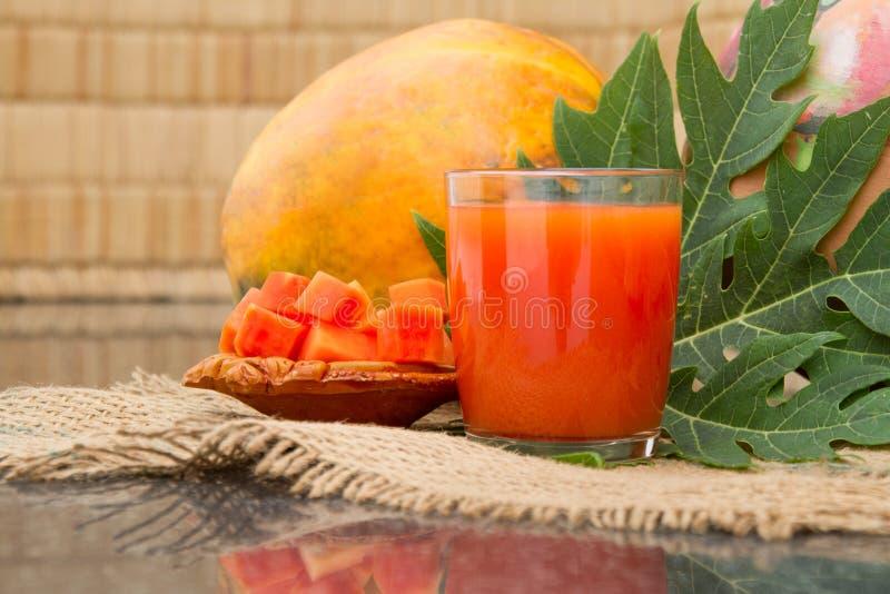 在玻璃的新鲜的木瓜汁用番木瓜果子、叶子和切片 库存照片