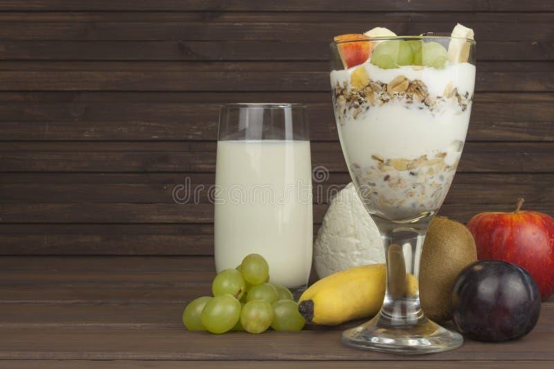 在玻璃的新鲜的牛奶和muesli在一张木桌上用早餐 燕麦粥用牛奶和凝乳,运动员的饭食 库存照片
