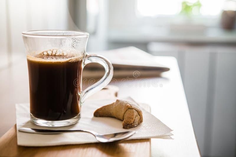 在玻璃的无奶咖啡与匙子和新月形面包在木桌上 库存图片