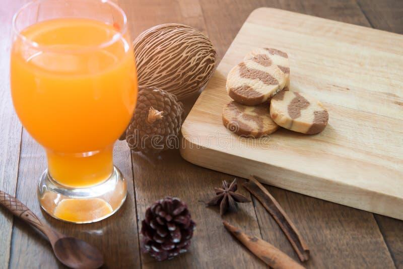 在玻璃的橙汁用在桌,温暖的口气上的曲奇饼在秋天 免版税库存图片