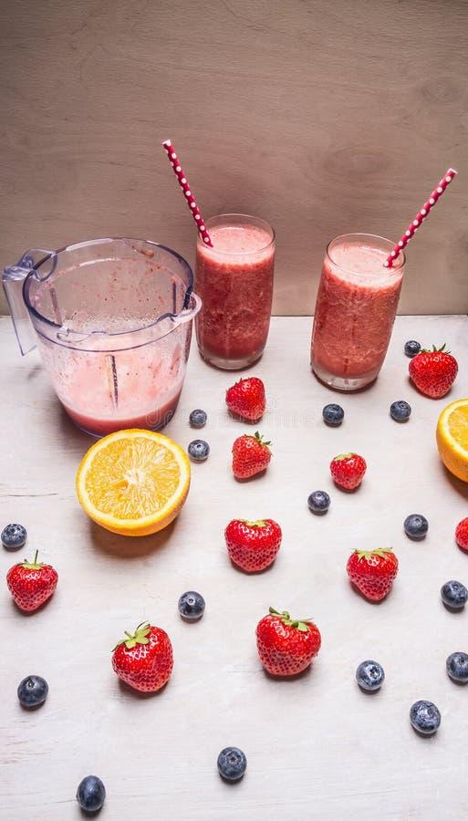 在玻璃的红色圆滑的人饮料与秸杆和果子在白色木背景,顶视图的莓果成份 免版税库存图片