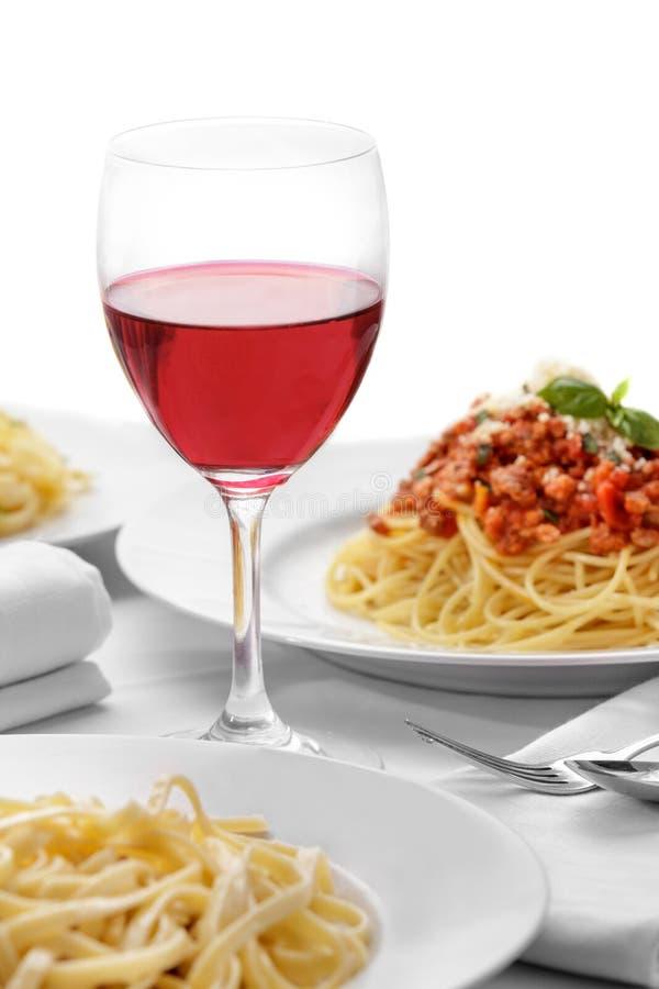 在玻璃的红葡萄酒与意大利面团烹调 免版税库存照片