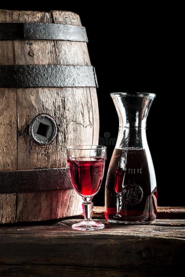 在玻璃的红葡萄酒和玻璃水瓶在老酿酒厂 库存图片