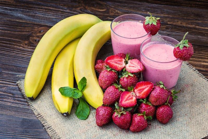 在玻璃的草莓和香蕉圆滑的人 新鲜的草莓 免版税库存照片
