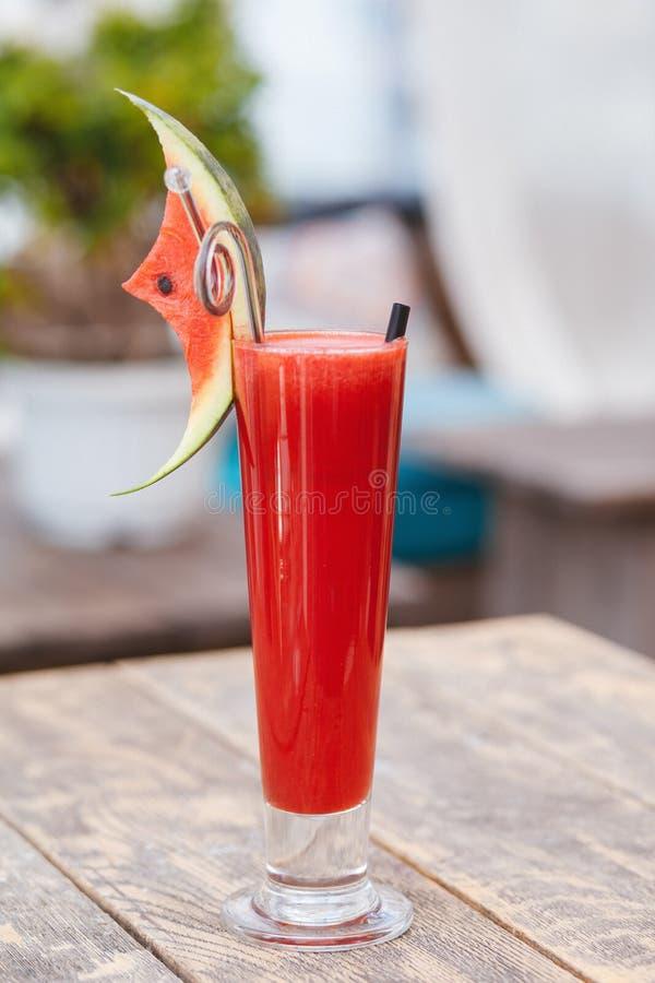 在玻璃的西瓜汁与切片在木桌上的西瓜 免版税库存照片