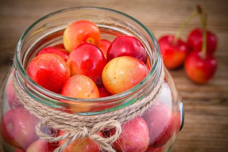 在玻璃的更加多雨的樱桃在木背景 库存照片