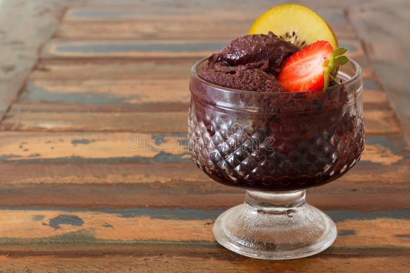 在玻璃的Acai黏浆状物质用草莓和猕猴桃在木桌上 库存照片