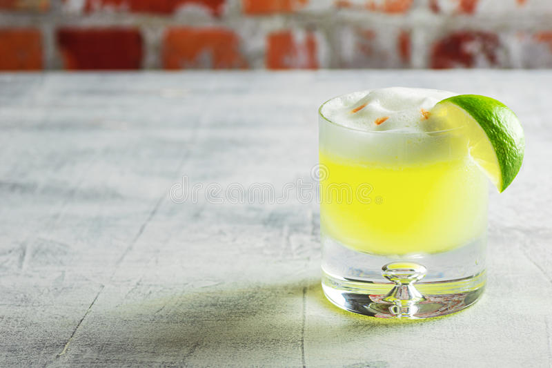 在玻璃的Pisco酸鸡尾酒与石灰 免版税库存照片
