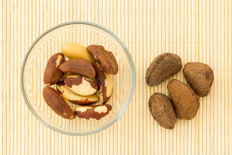 在玻璃碗和某一坚果的巴西坚果在壳 免版税库存照片