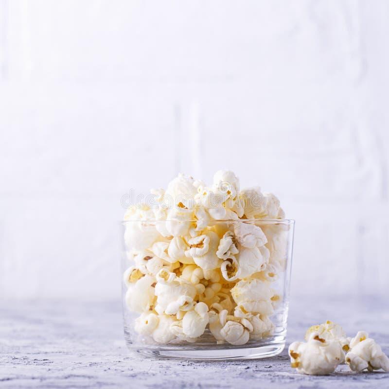 在玻璃碗的玉米花在白色背景 库存图片