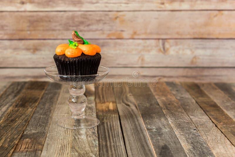 在玻璃立场的南瓜杯形蛋糕 库存照片