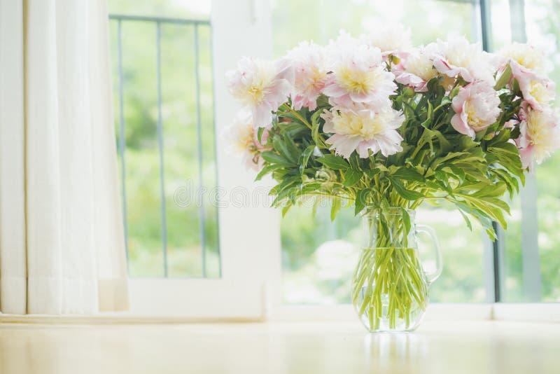 在玻璃花瓶的大美丽的淡粉红的牡丹花束在窗口背景 与花和花瓶的轻的家庭装饰 免版税库存照片