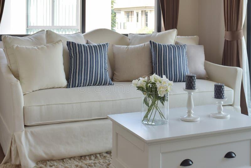 在玻璃花瓶的装饰花有在一个偶然沙发的蓝色镶边枕头的 库存照片