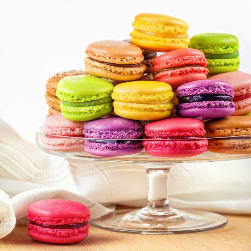 在玻璃蛋糕的法国五颜六色的macarons站立 免版税库存照片