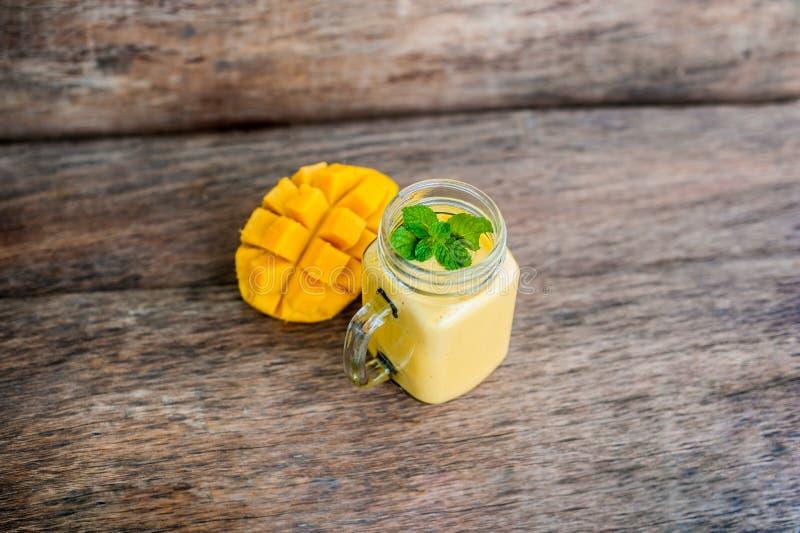 在玻璃金属螺盖玻璃瓶和芒果的芒果圆滑的人在老木背景 芒果震动 库存图片