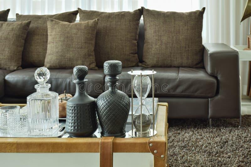 在玻璃顶面桌上的饮料被设置的水晶和sandglass在客厅 免版税库存照片