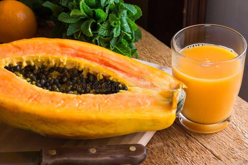 在玻璃,果子的新近地做的木瓜汁切成了两半,刀子,在木厨房用桌上的新鲜薄荷 免版税库存照片