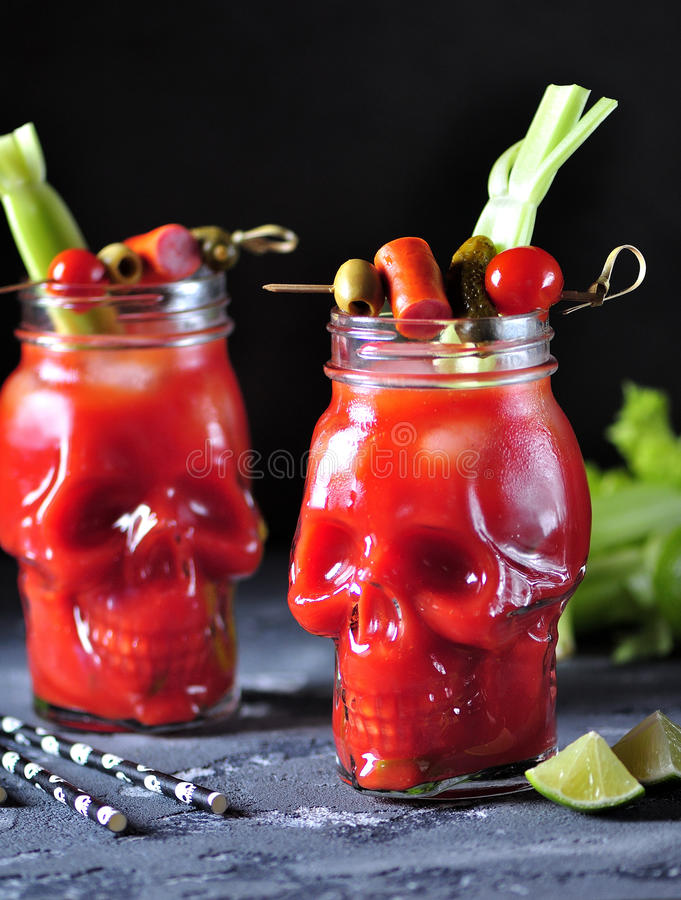 在玻璃头骨的血玛莉酒鸡尾酒用芹菜杆、桃红色盐、石灰和点心从罐装菜 免版税库存照片