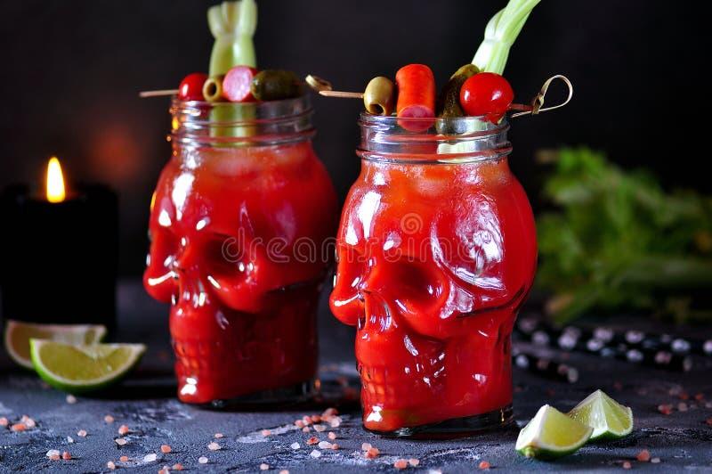 在玻璃头骨的血玛莉酒鸡尾酒用芹菜杆、桃红色盐、石灰和点心从罐装菜 库存照片