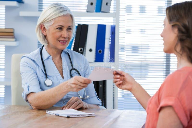 在医疗办公室篡改给处方她的患者 免版税库存图片